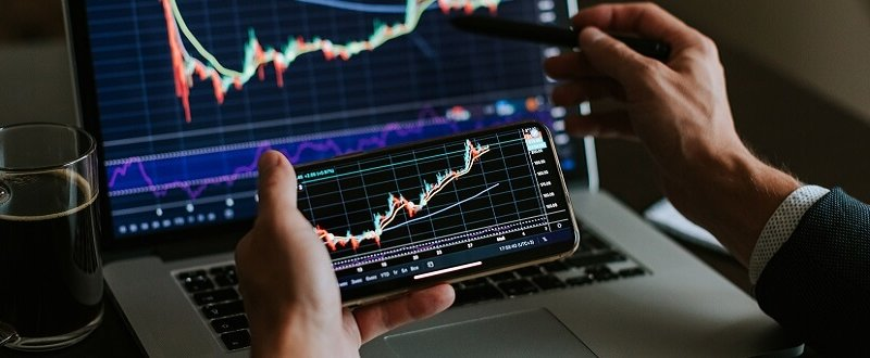 investment stockbroker profit analysis. Stock trading graph price prediction and profit gain. Manager using multiple devices, laptop, phone. Trade graph chart.
